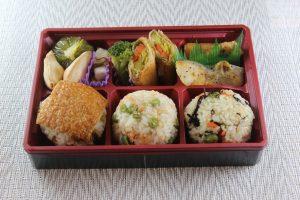 ▼「ガッツリ系」のお弁当。主菜は、さつまいもの肉巻きと鱈(たら)のムニエル。 地元野菜が10種類ほど使われています。